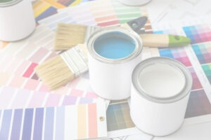 paint cans alongside paint brushes and color swabs