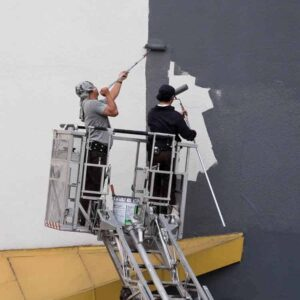 painters painting exterior of commercial building