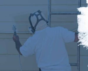 Painter spraying exterior of house with fresh paint