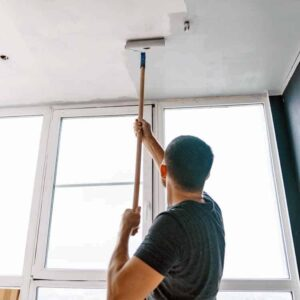 painter painting ceiling of room
