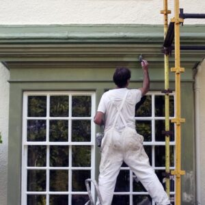 painter working on external paint job on house.